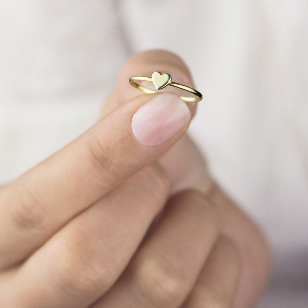 a yellow gold ring with a tiny heart