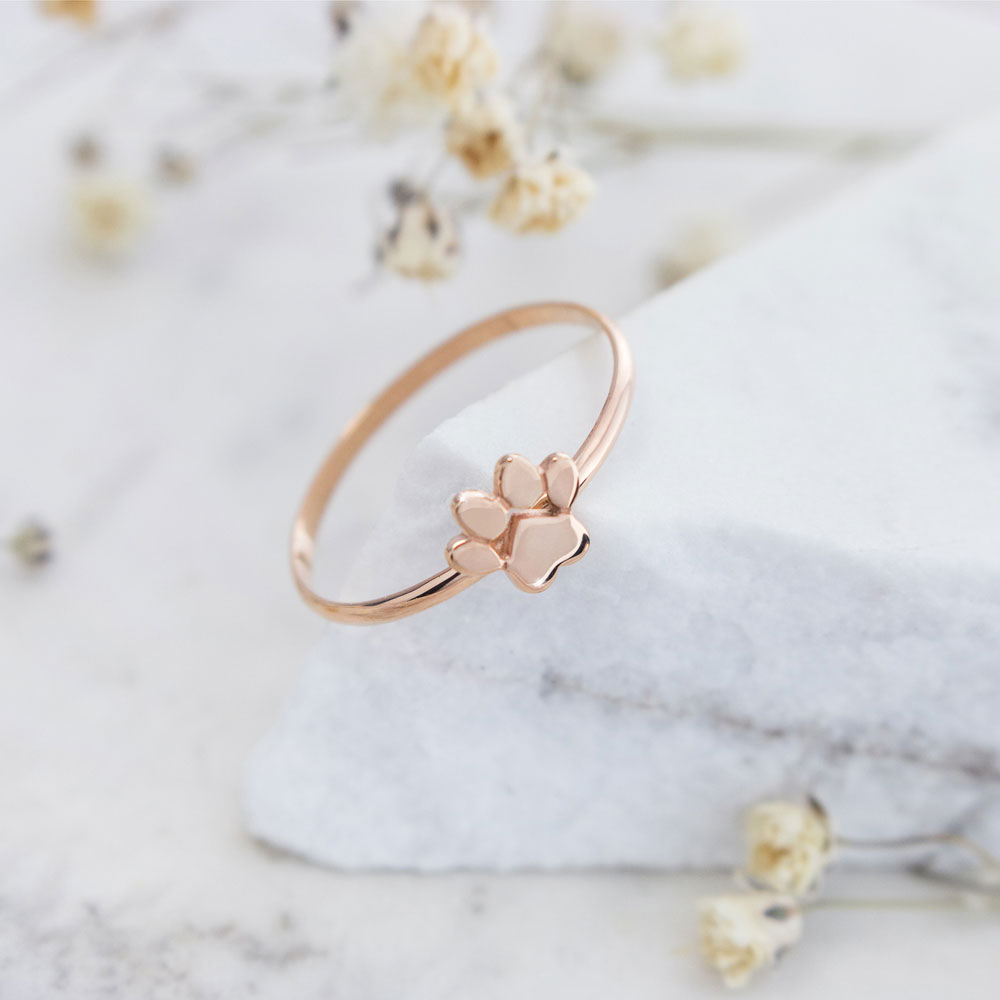 a rose gold ring with a tiny paw print