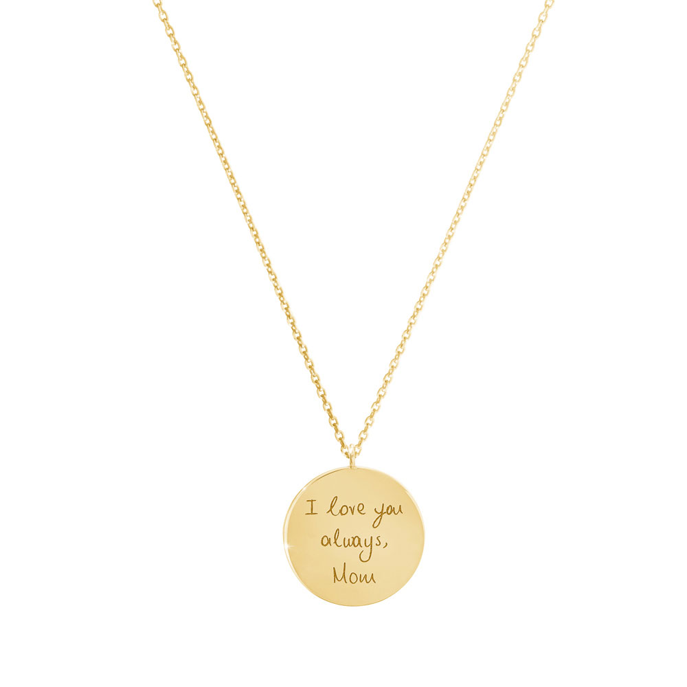 A small engraved disc necklace in yellow gold