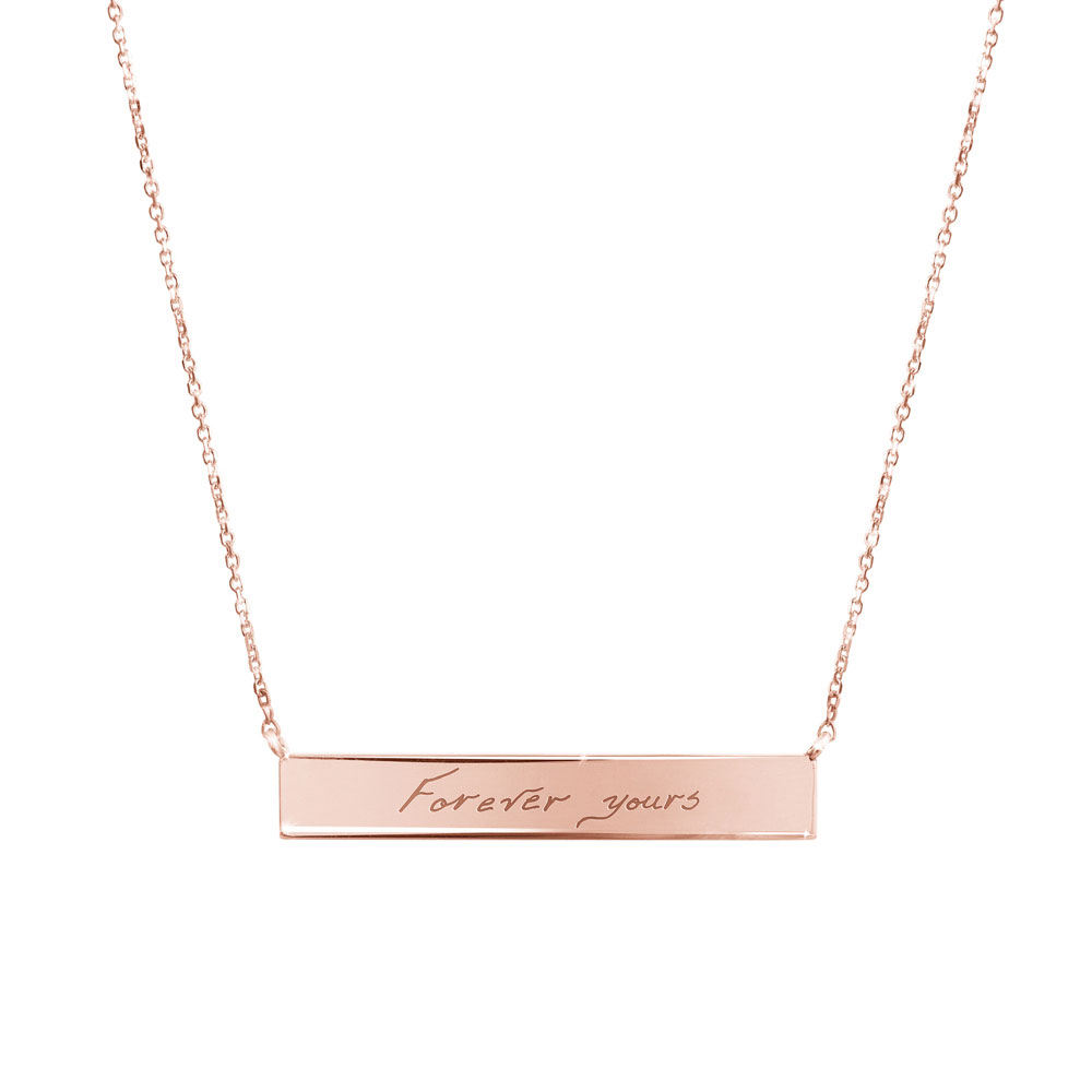 A rose gold bar necklace with a personalized message