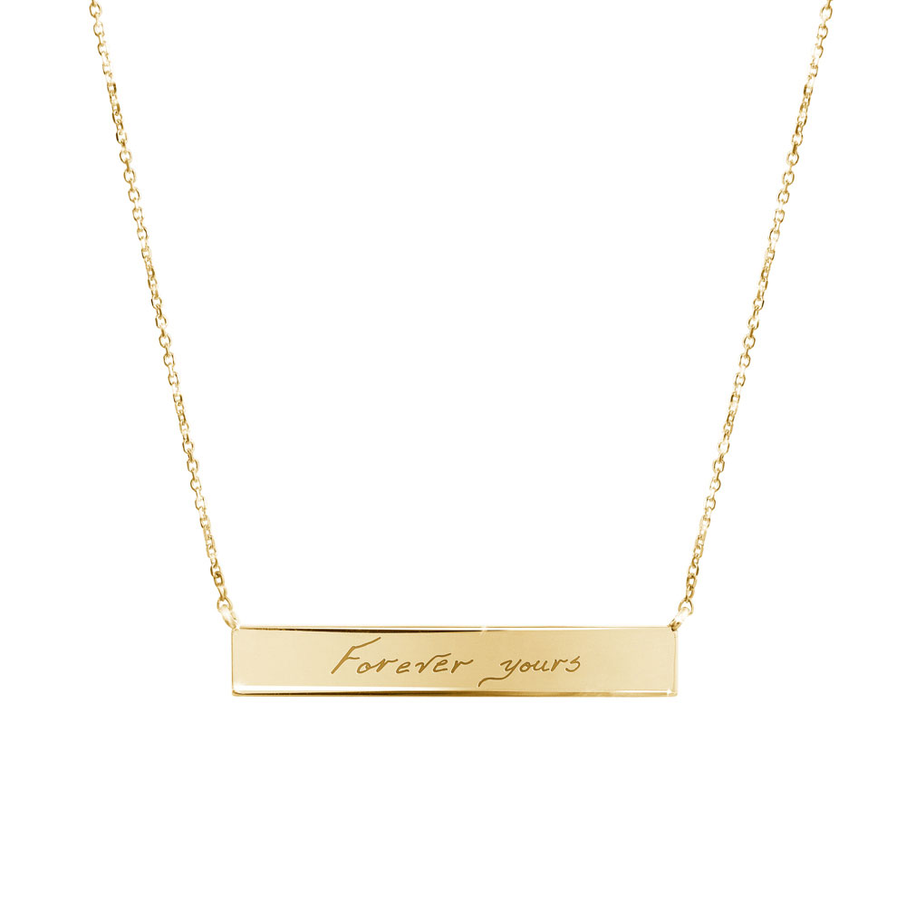 A yellow gold bar necklace with a personalized message
