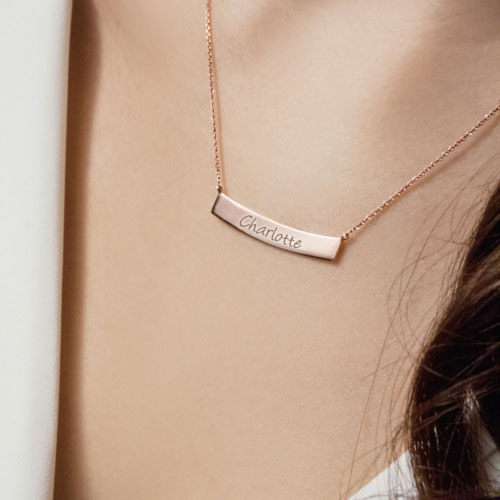 Gold Curved Bar Necklace with Custom-Engraving In Rose Gold Worn By A Woman