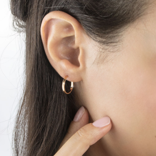 Tiny Flat Circle Hoop Earrings in Rose Gold Worn By A Woman